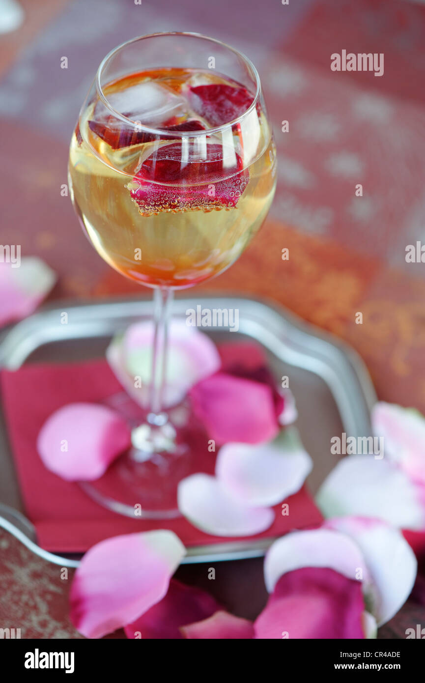 Glas of champagne with rose petals, rose prosecco - Stock Image