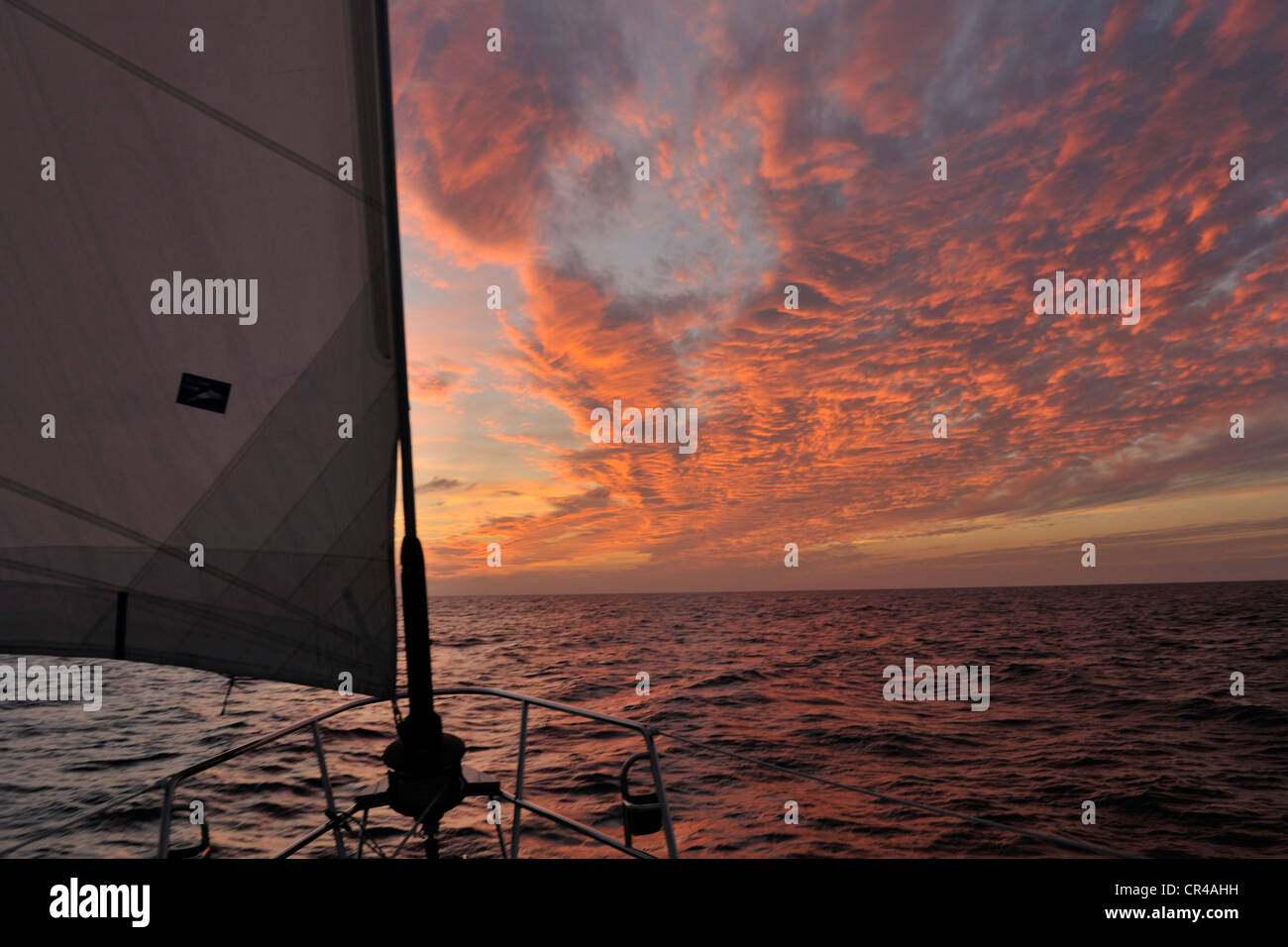 A cruising yacht sails south west through the Caribbean Sea at sunset. - Stock Image