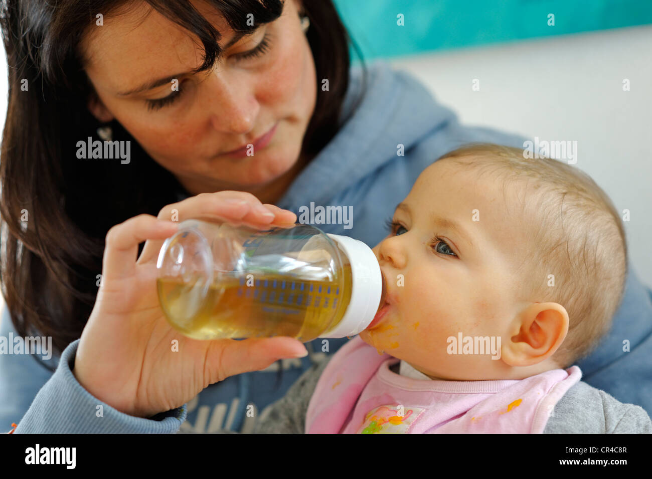 Baby, six months, drinking from a bottle held by its mother - Stock Image