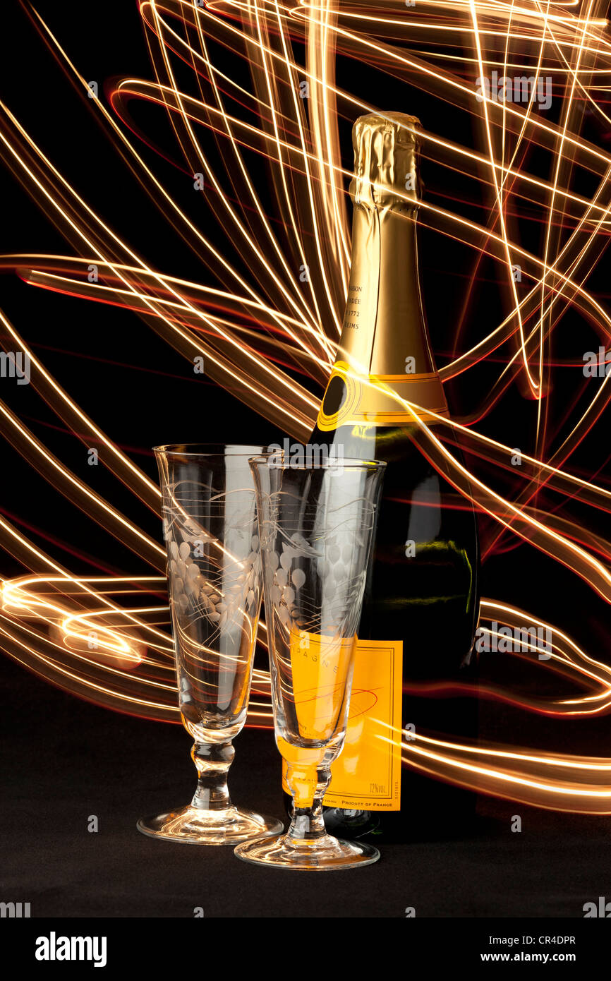 Red and gold light trails swirling around a bottle of Champagne and two Champagne Flute glasses - Stock Image