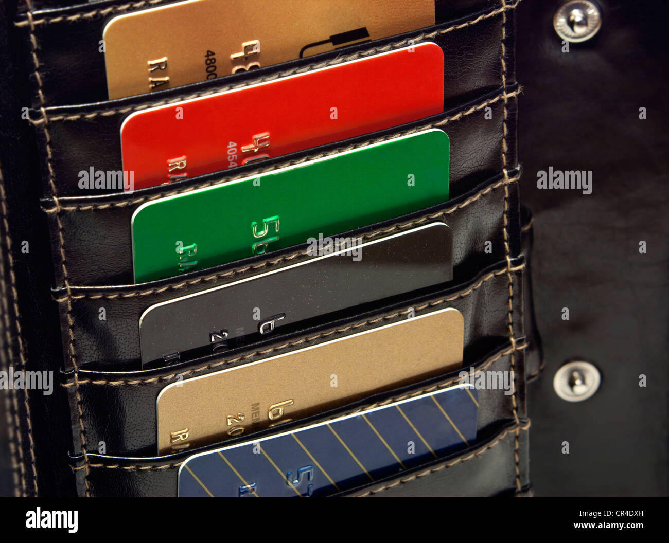 Several Multicolored red green black blue gold credit cards in the black wallet. - Stock Image