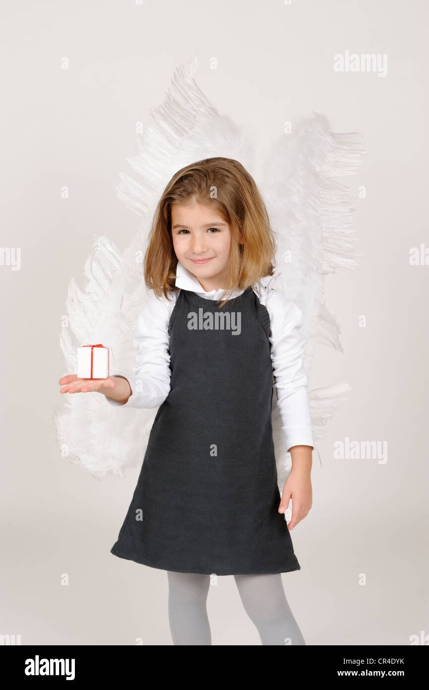 Girl with angel wings with Christmas present - Stock Image