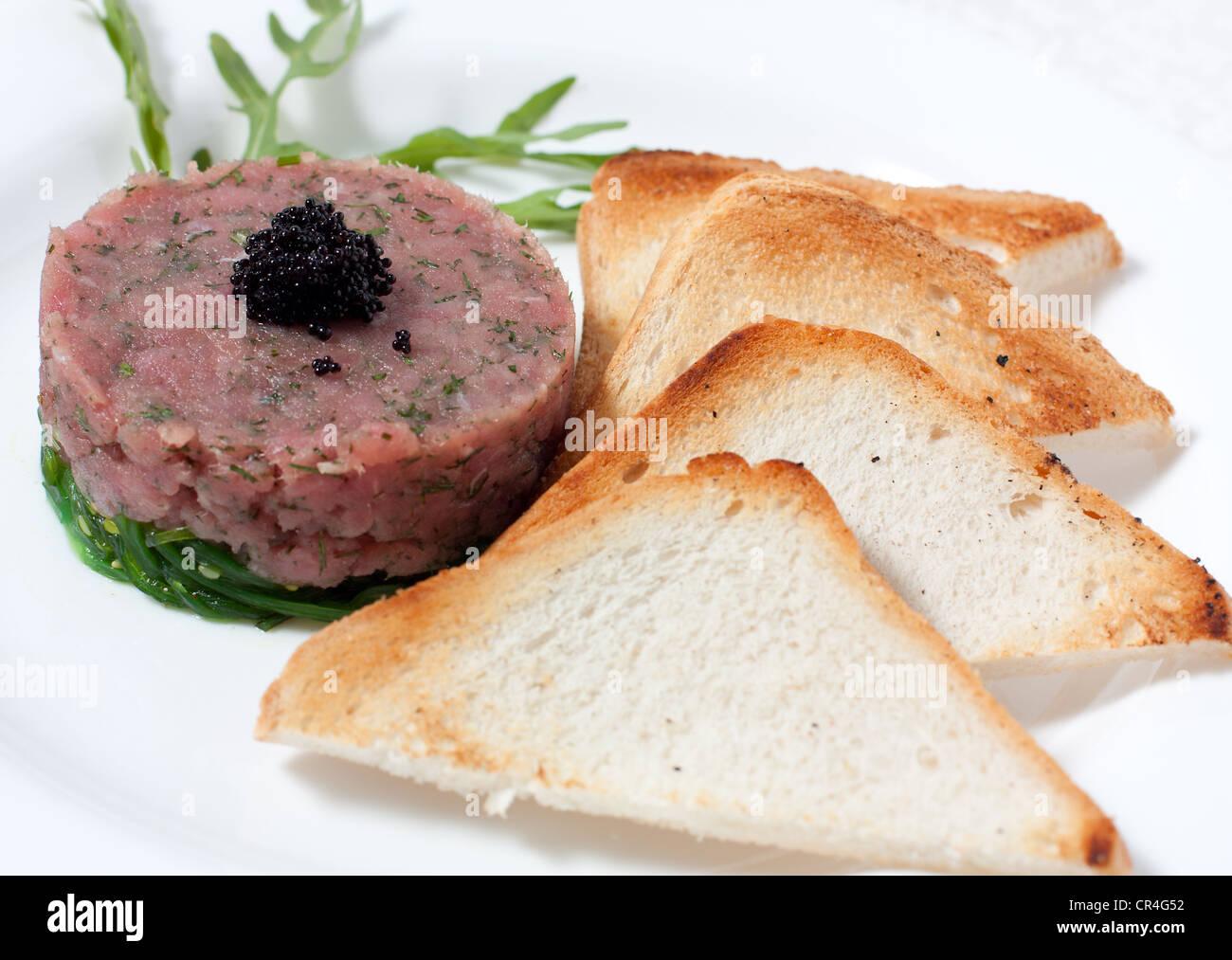 Croutons and a salad with salmon, seaweed and caviar - Stock Image