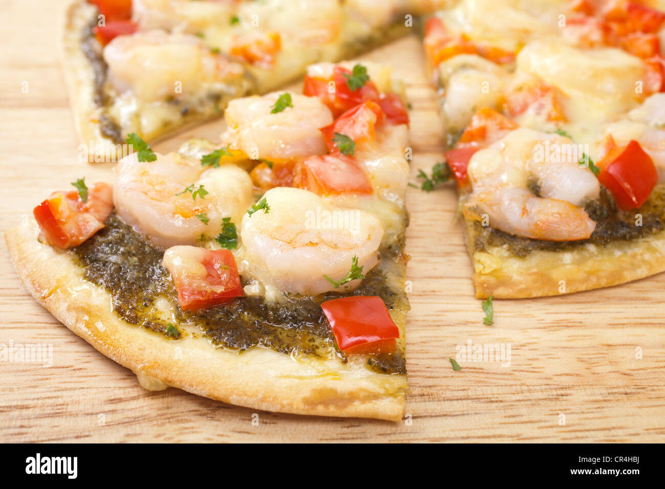 Crispy based pizza topped with prawns, red pepper, mozzarella and basil pesto. - Stock Image