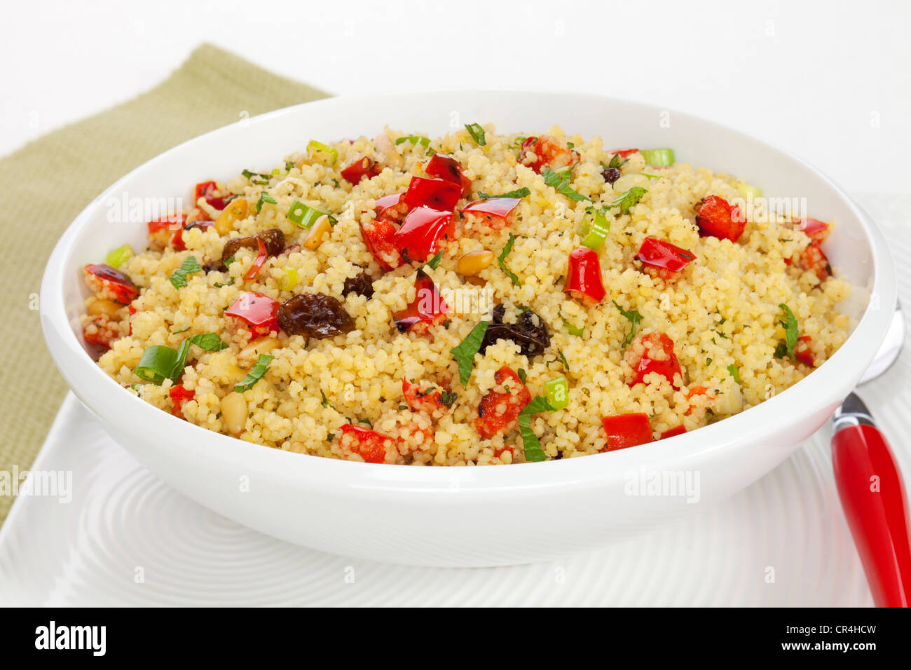 Couscous salad, with roasted red peppers, raisins, pine nuts, green onion and mint. Shallow DOF, focus on centre. - Stock Image