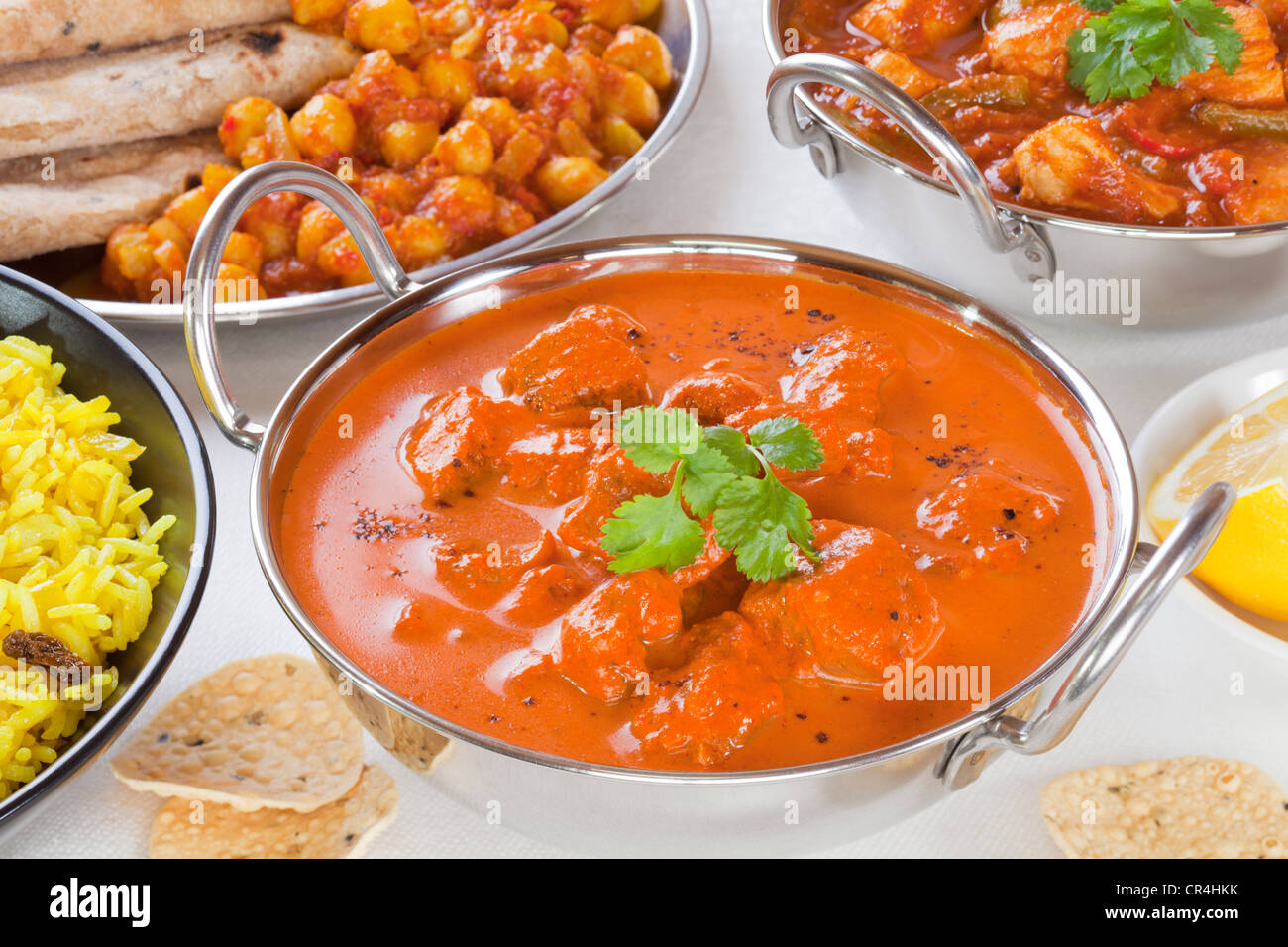 Selection of curry dishes with rogan josh, pillau rice,chana dhal,chicken jalfrezi and poppadums. - Stock Image