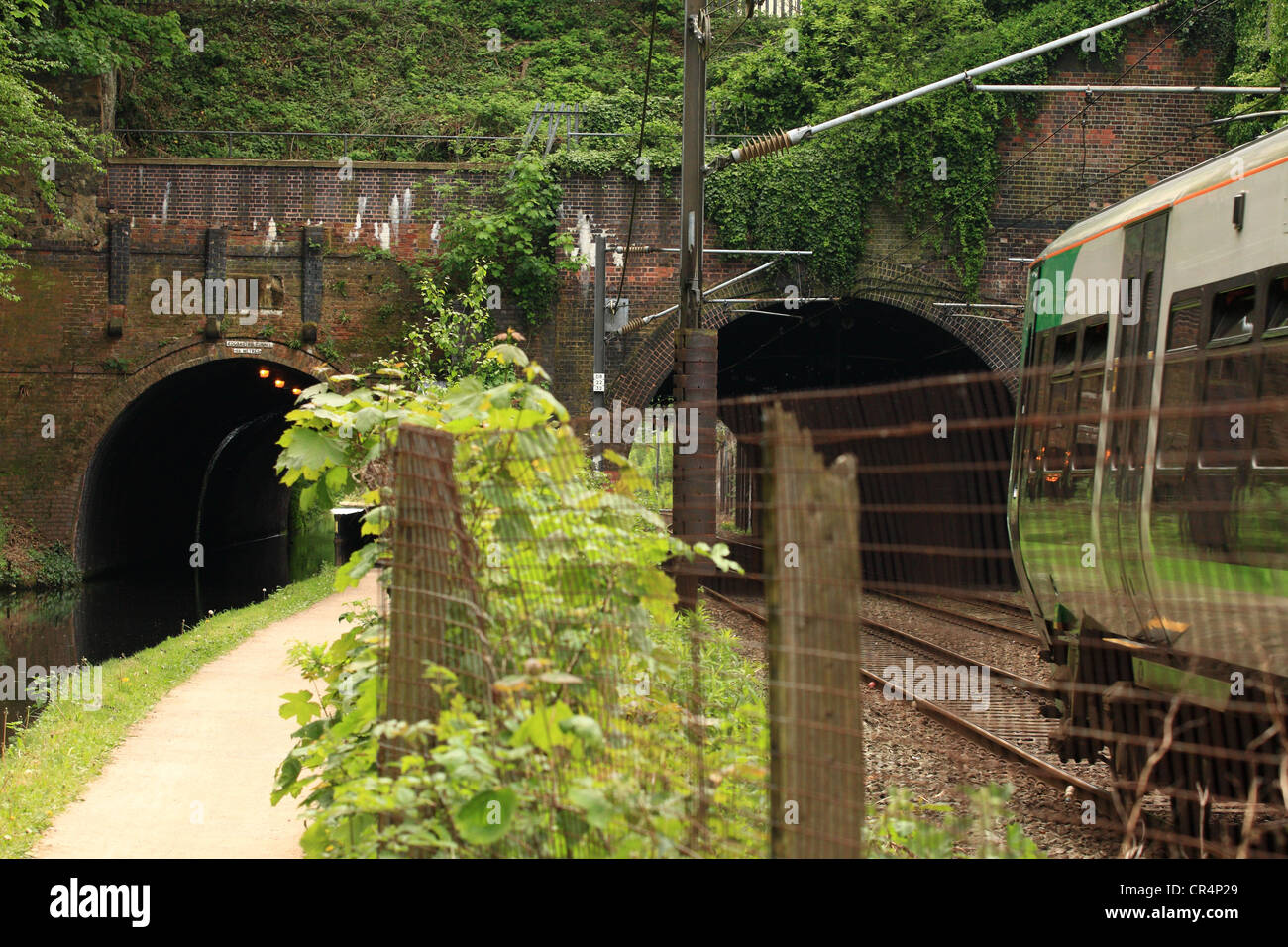 a bridge crossing a railway and a canal and a train approaching one of the bridge arches Stock Photo