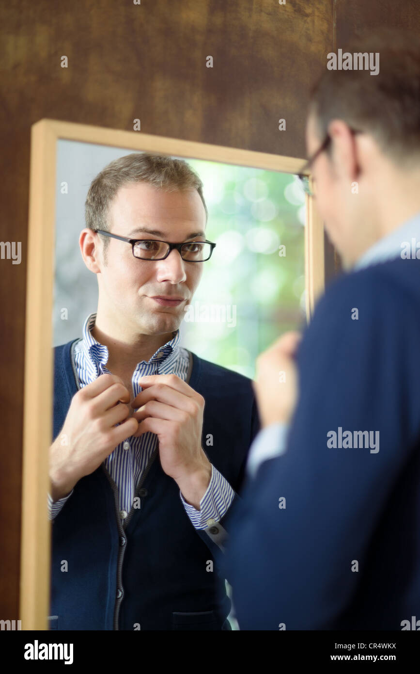Portrait of young man with glasses getting ready, dressing up and looking at mirror - Stock Image
