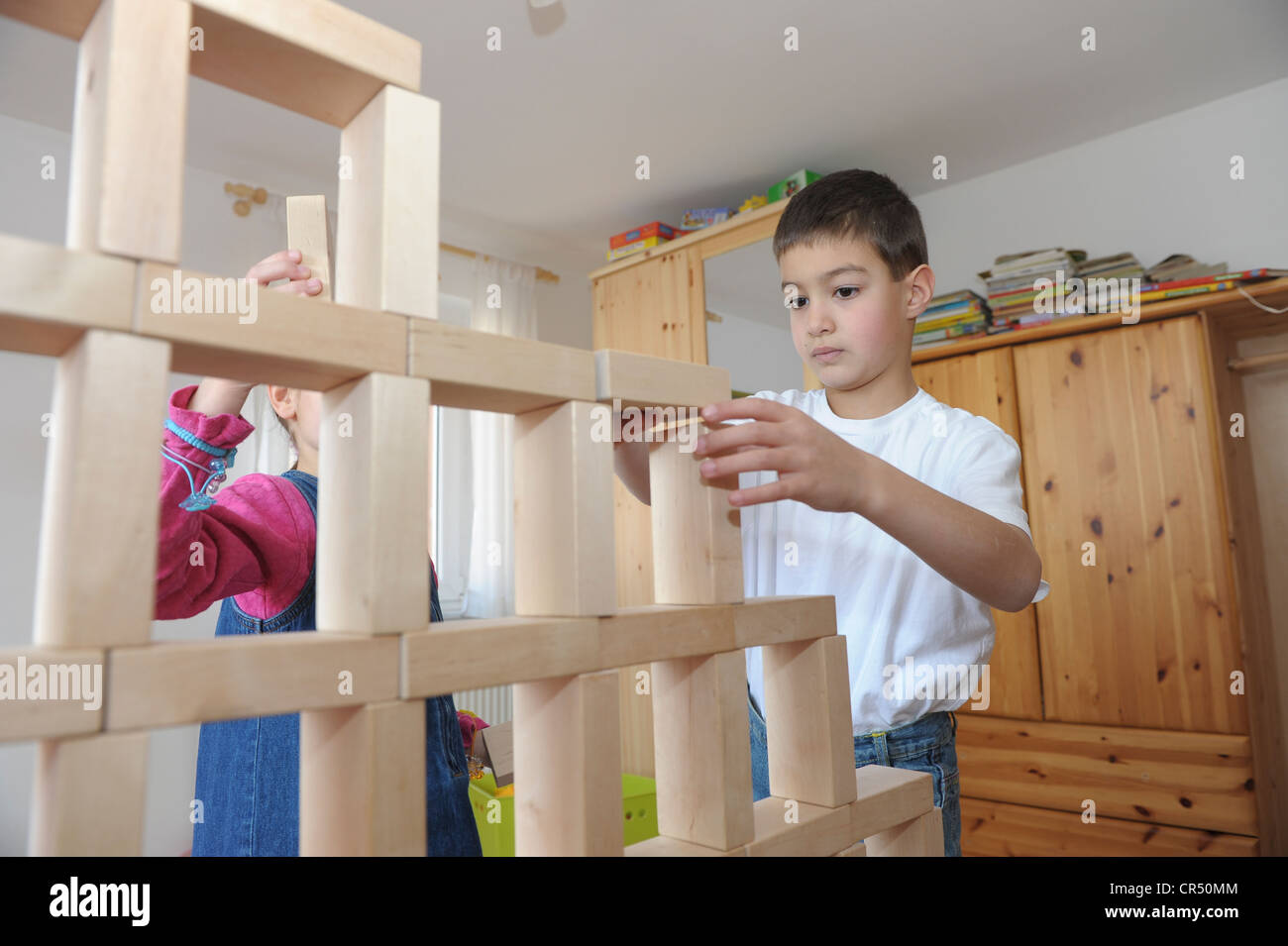 Girl and boy, 6 and 7 years, playing with toy blocks - Stock Image