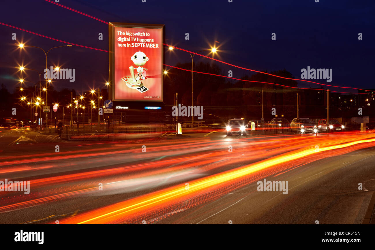 Outdoor roadside advertising panel showing a digital switchover creative. Car lights pass the panel on a main road - Stock Image