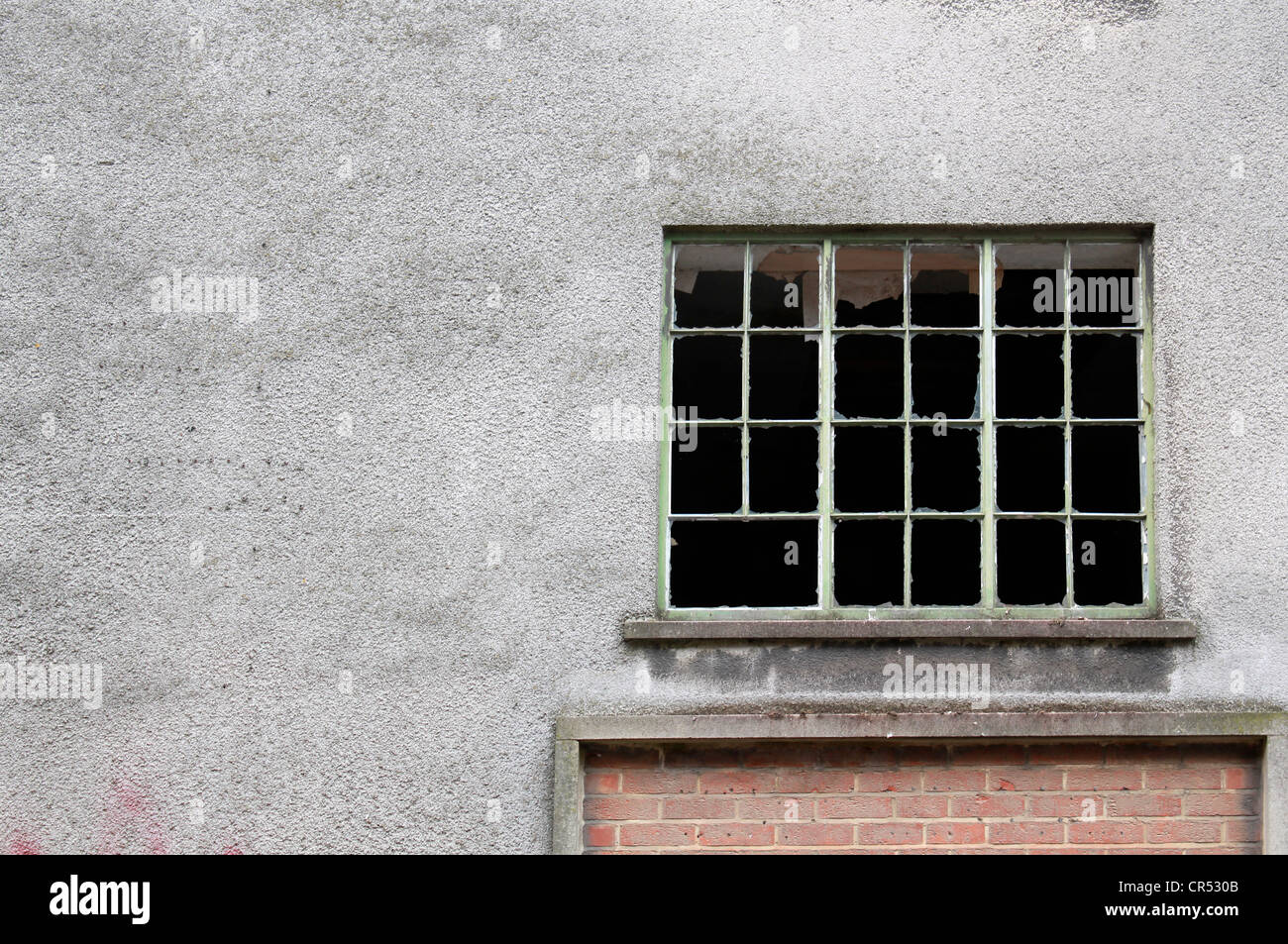 Broken window in derelict factory with blank space - Stock Image