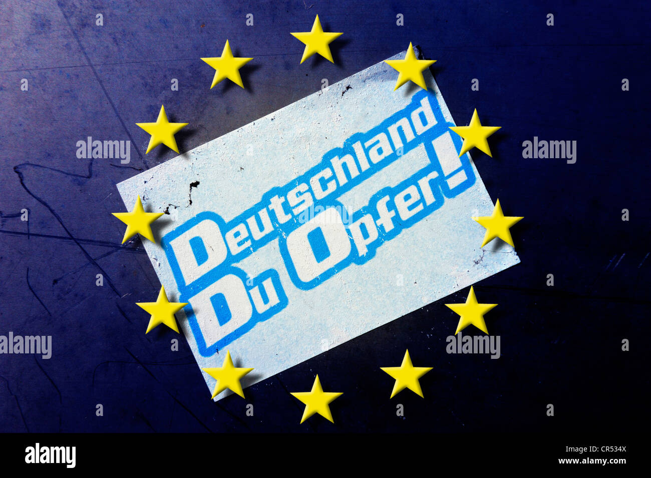 EU stars and sticker on a wall, 'Deutschland, Du Opfer!', German for 'Germany, you are a victim' - Stock Image