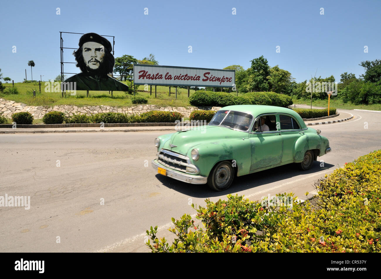 Vintage car in front of revolutionary propaganda, 'Hasta la victoria siempre', Spanish for 'ever onward - Stock Image