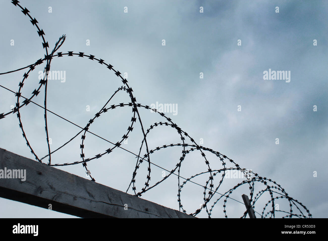 Barbed Wire Fence against threatening sky - Stock Image