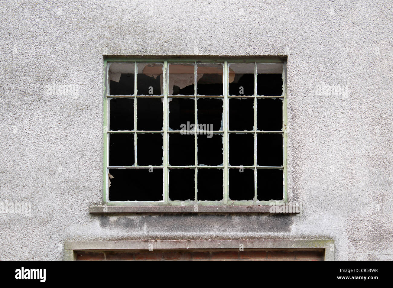 Broken window in derelict factory wall - Stock Image