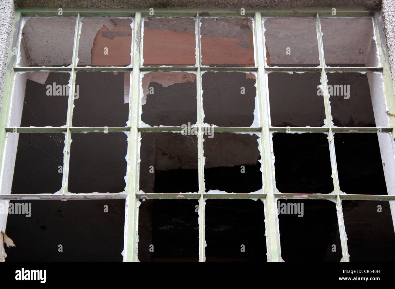 Broken window in derelict factory - Stock Image