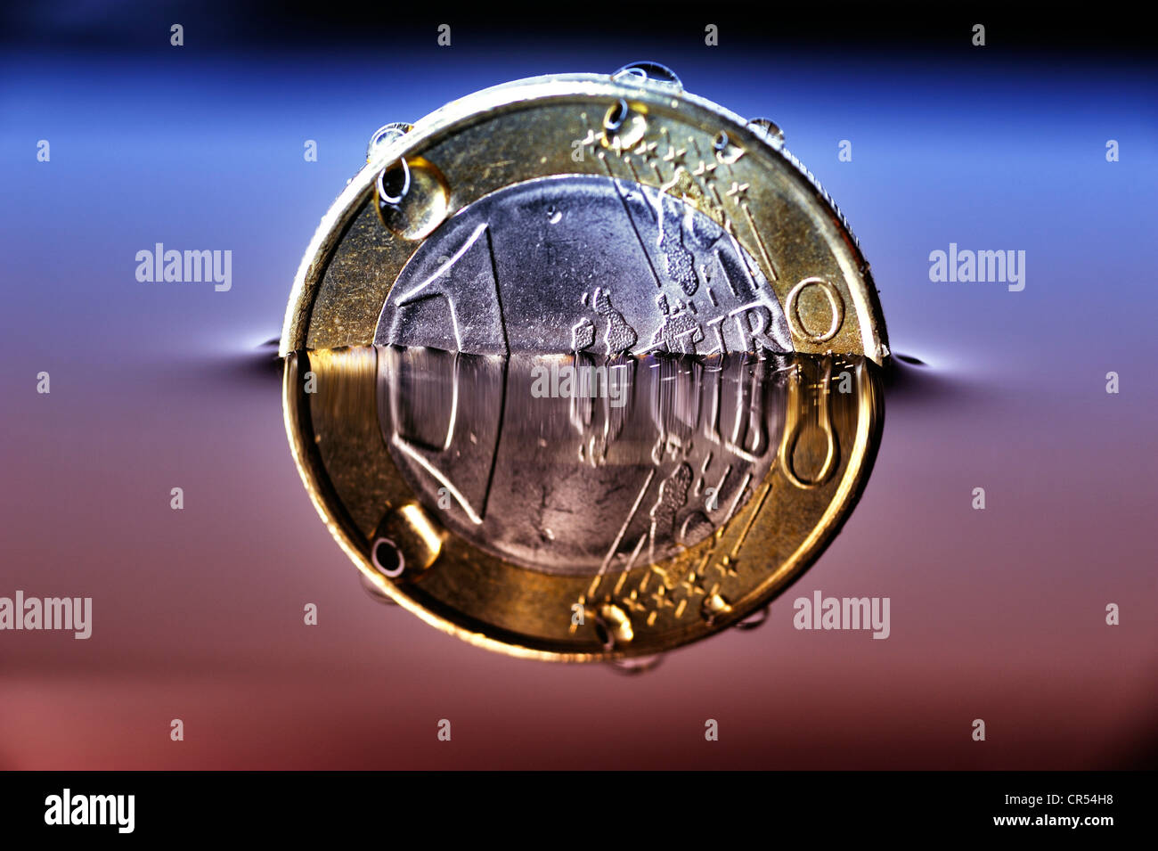 A euro coin sinking in water, symbolic image for the debt crisis in europe - Stock Image