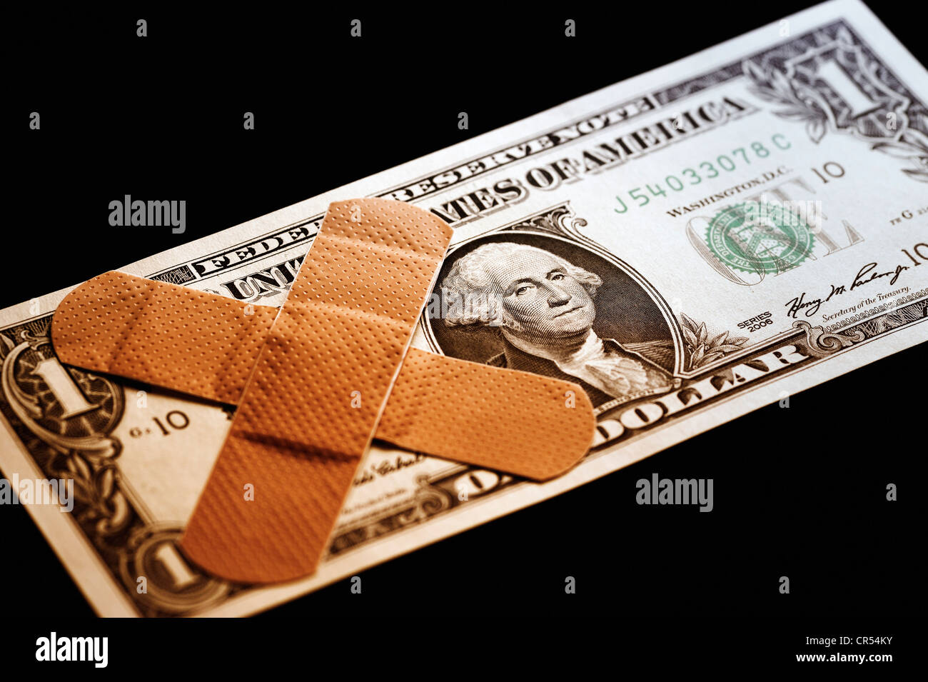 U.S. dollar with band-aid, symbolic image for the national debt of the USA - Stock Image