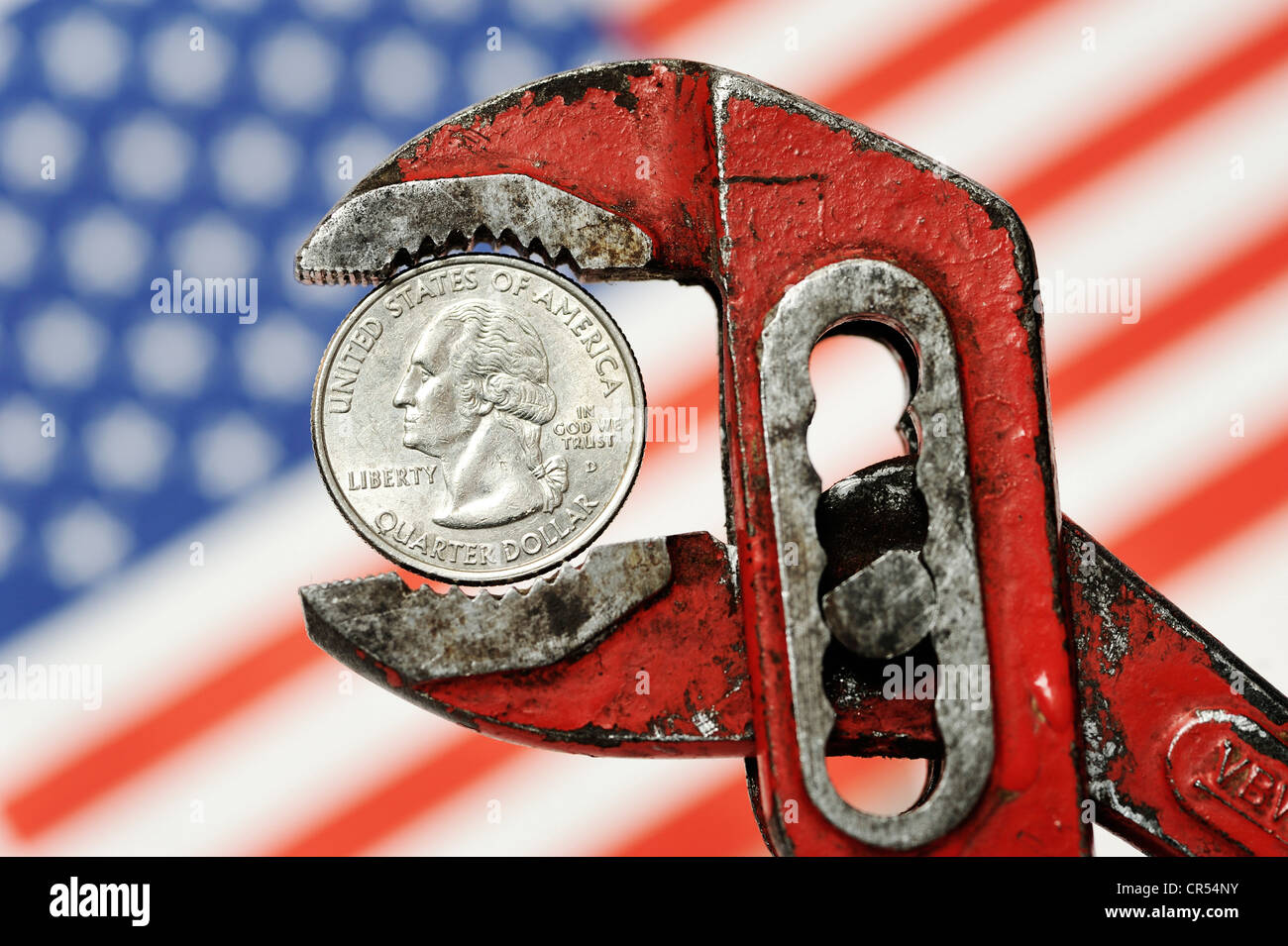 Quarter dollar in a debt wrench, symbolic image for the U.S. national debt - Stock Image