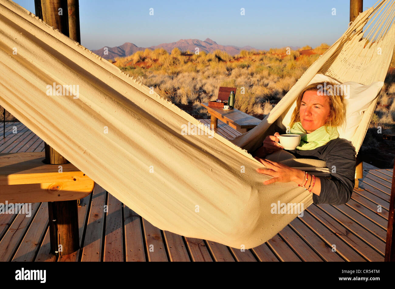 Tourist in a hammock in front of a chalet of the Wolwedans Dune Lodge in the Namib Rand Nature Reserve, Namib Desert, - Stock Image