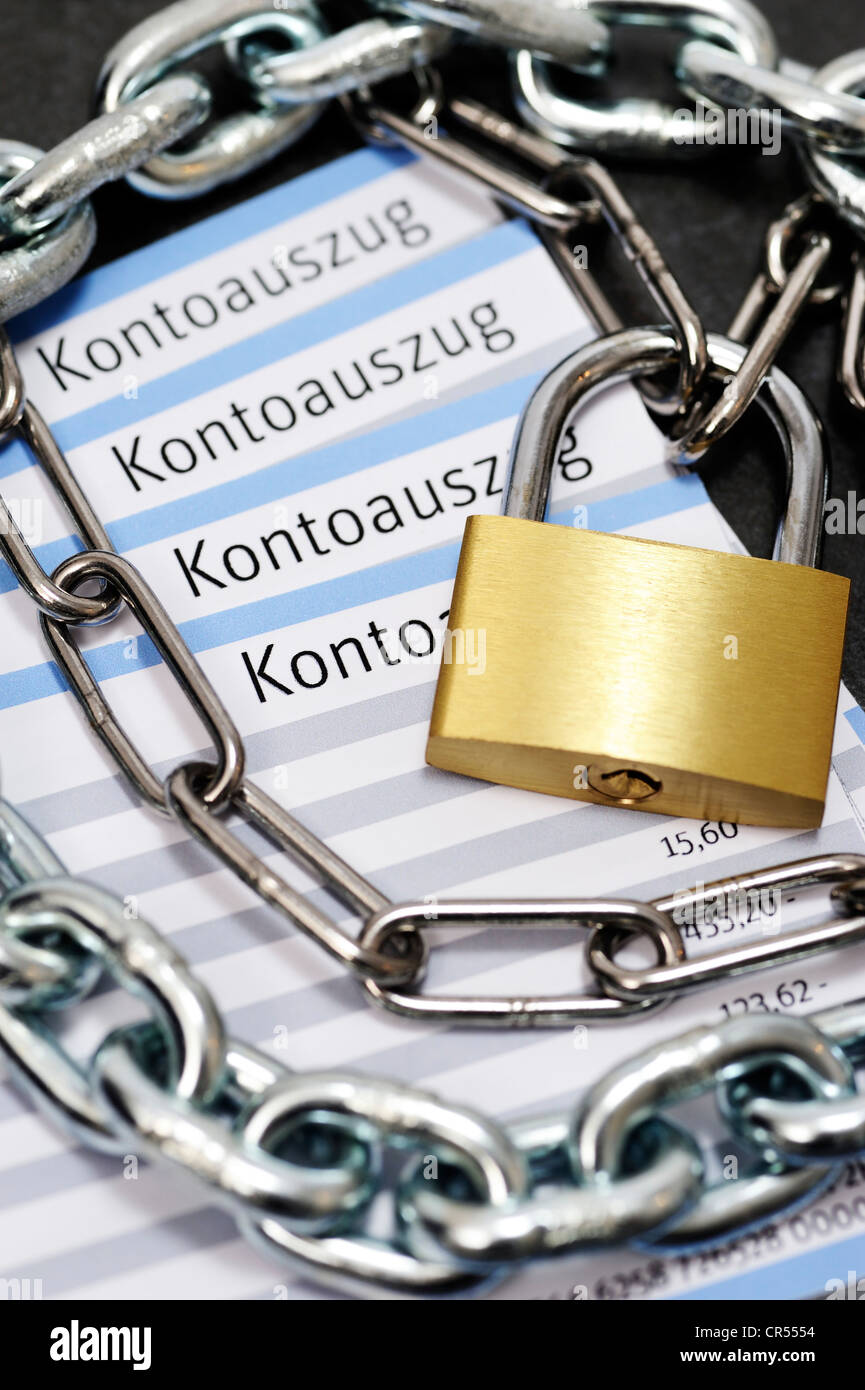 Bank statements with chains and a padlock, symbolic image - Stock Image