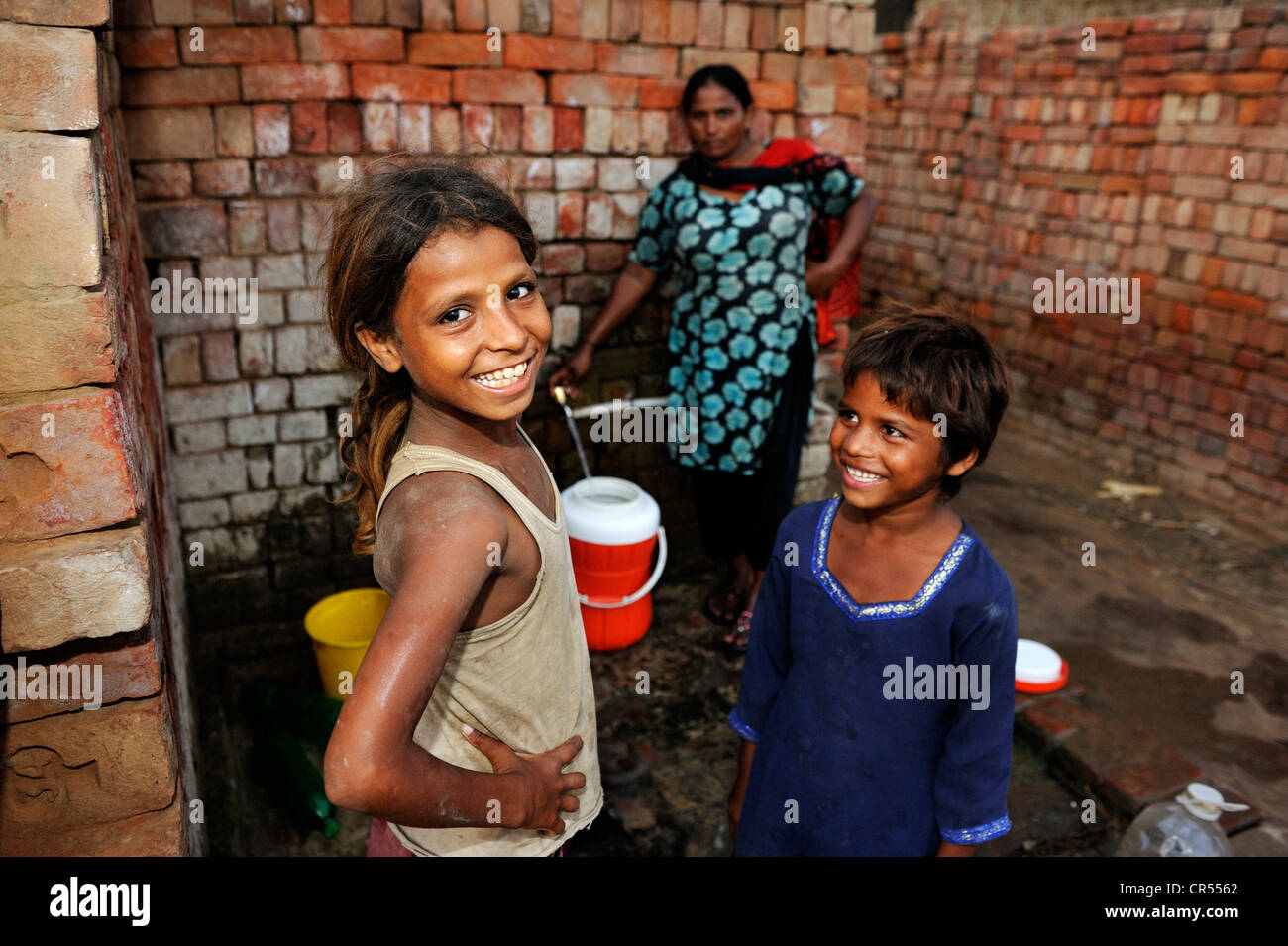 Woman and girls collecting water from a tap, they live and work with their family under the slavery-like practice Stock Photo