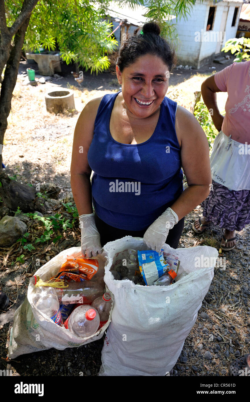 Woman with rubbish bags full of rubbish that was spread across the entire village by the flood disaster of October - Stock Image