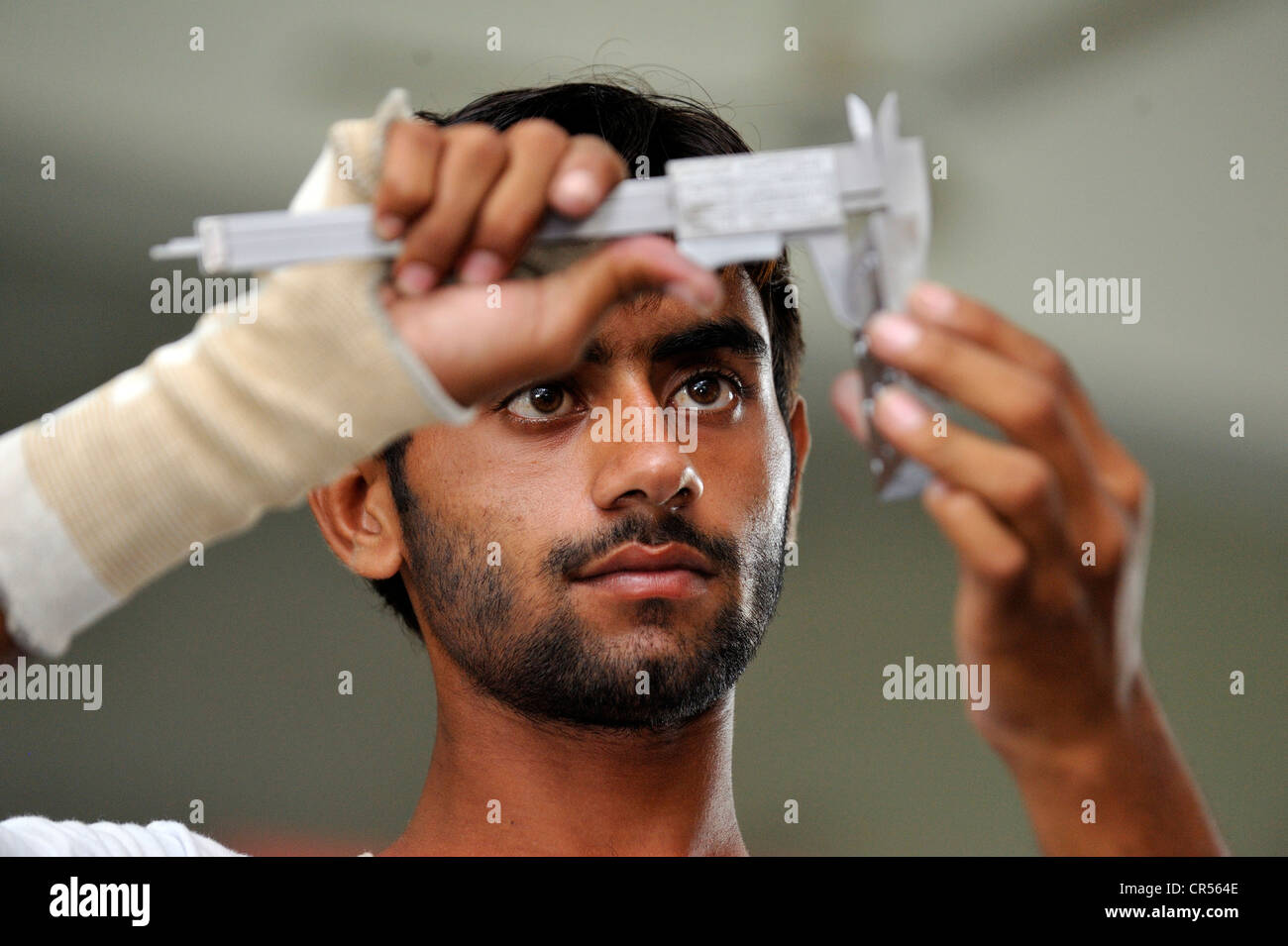 Vocational training as a metalworker, vocational student checking his work with a steel ingot for accuracy, Youhanabad, - Stock Image