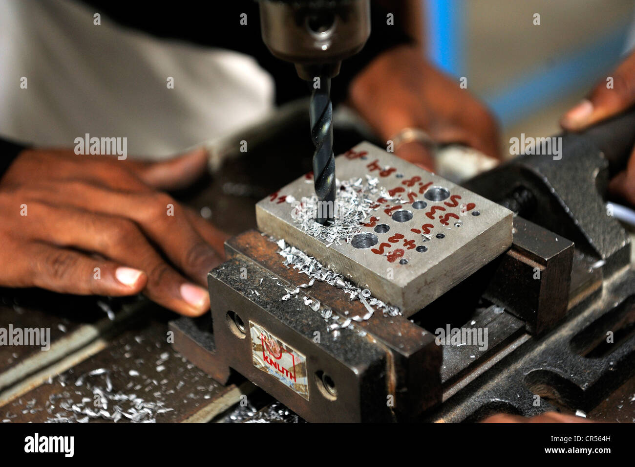 Vocational training as a metalworker, vocational student drilling different size holes in a steel ingot, Youhanabad, - Stock Image