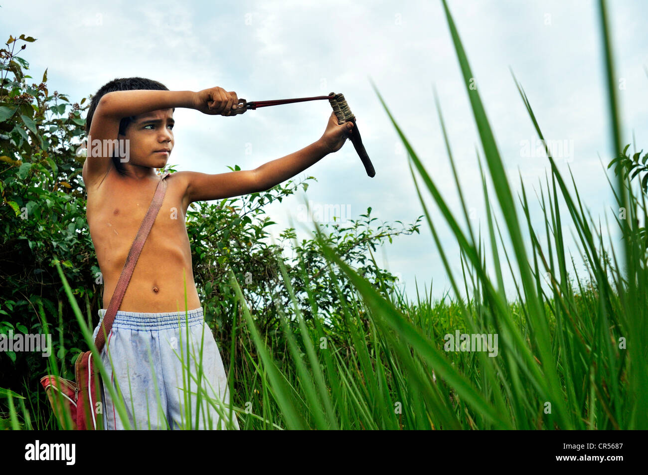 Boy hunting songbirds with a slingshot, Acampamento 12 de Otubro landless camp, Movimento dos Trabalhadores Rurais - Stock Image