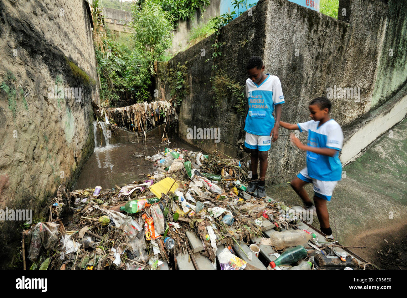 Residents of the slum district of Favela Morro da Formiga standing beside waste in an exposed sewer canal, Tijuca - Stock Image