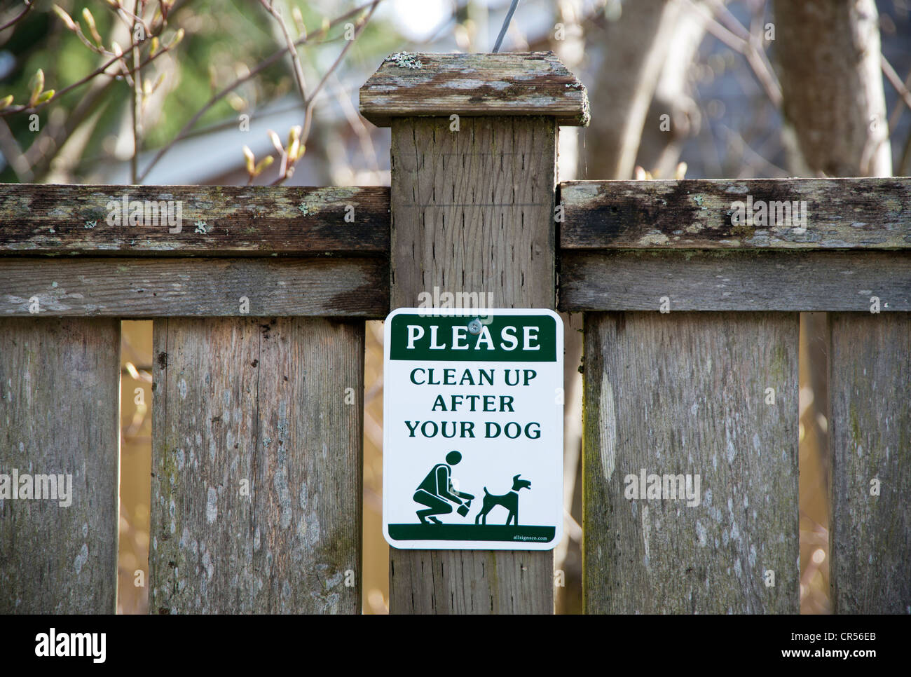 Sign on a fencepost asking people to clean up after their dog - Stock Image