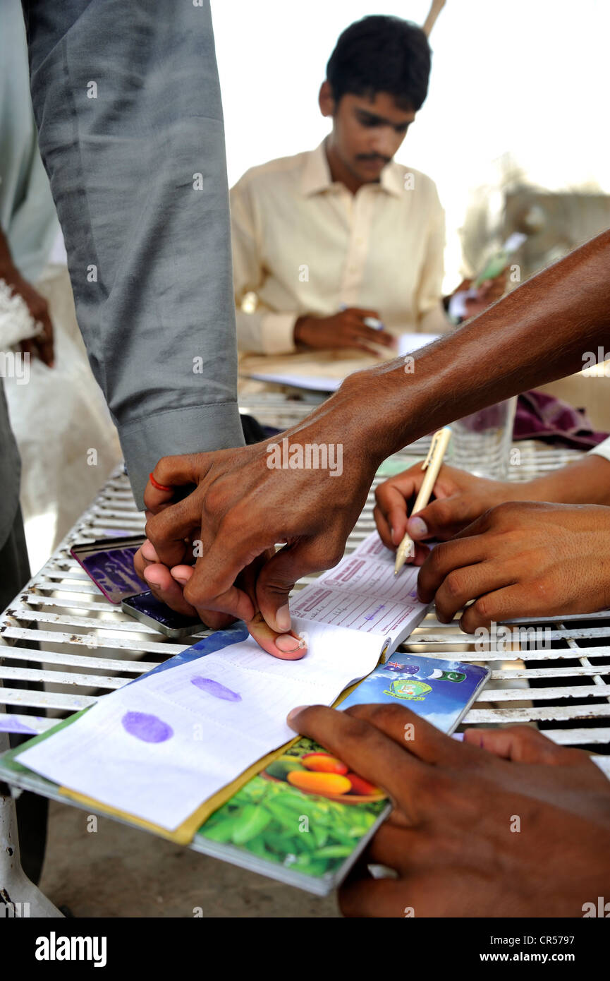 Distribution by a charity organisation after the flood disaster in 2010, beneficiaries signing with their fingerprint, - Stock Image