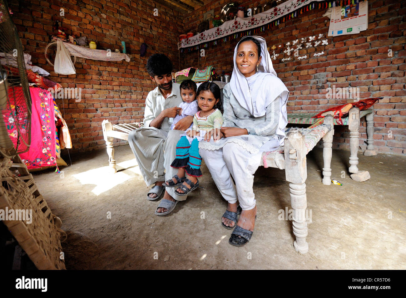 Family sitting in a new house made of bricks that they received from a relief organisation, their old house was Stock Photo