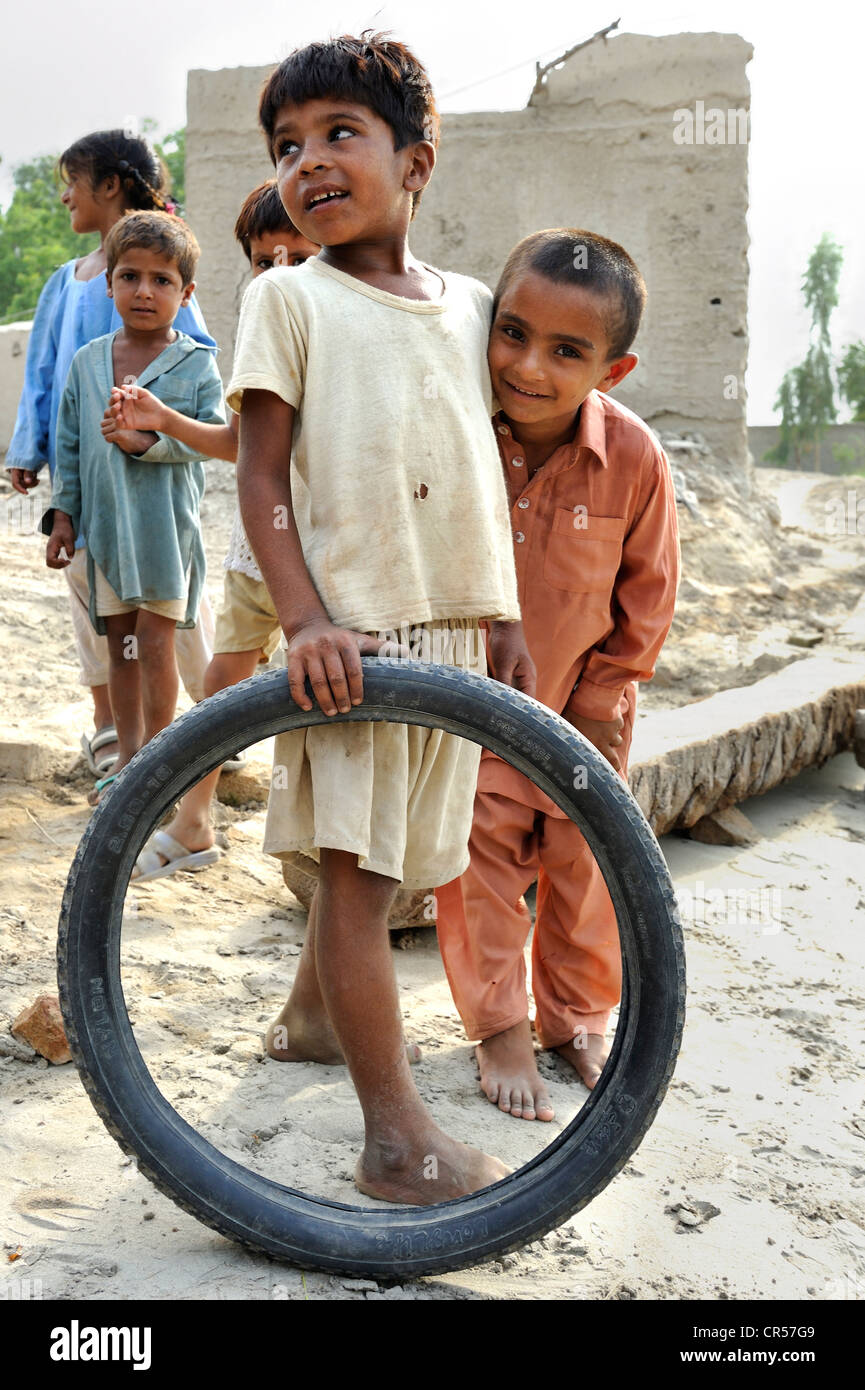 Children playing with a motorcycle tyre, village of Basti Lehar Walla, Punjab, Pakistan, Asia - Stock Image