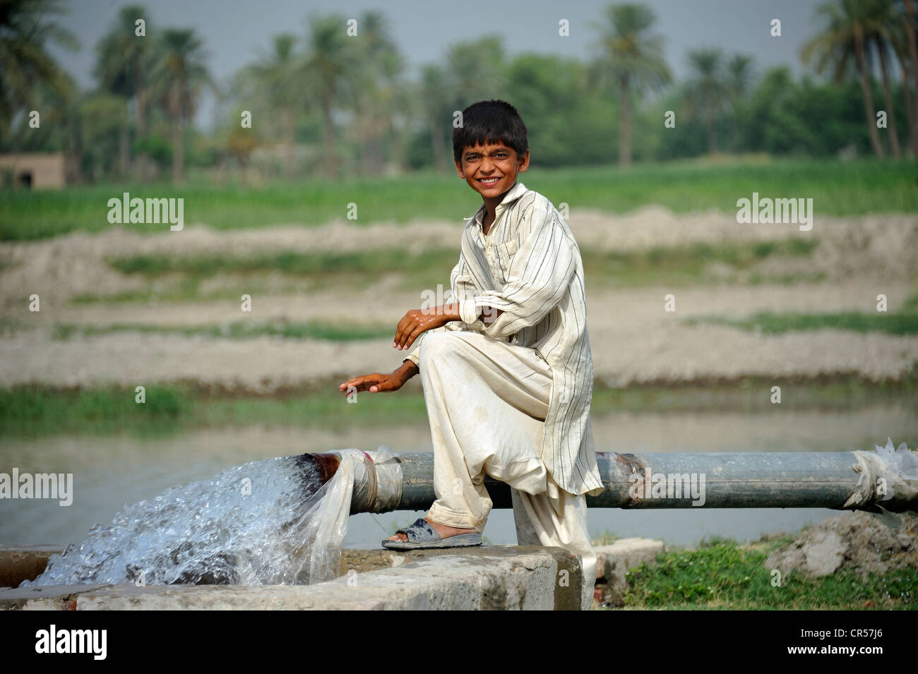 Boy standing at the catchment of a spring that is fed by a water pipe, Basti Lehar Walla village, Punjab, Pakistan, - Stock Image