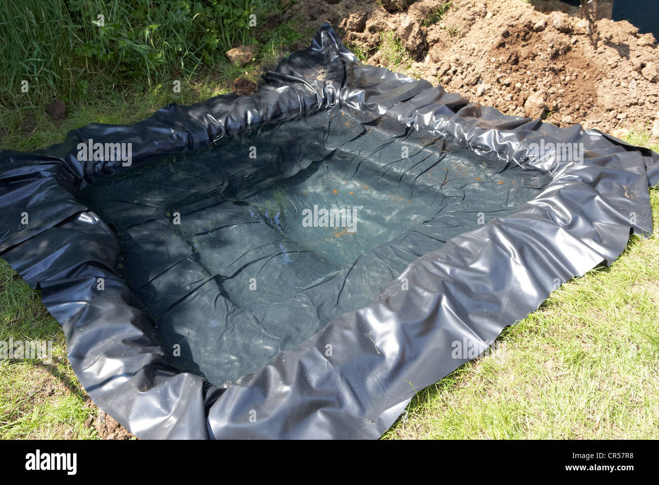 pond liner filled with water to create a pond in a garden in the uk - Stock Image