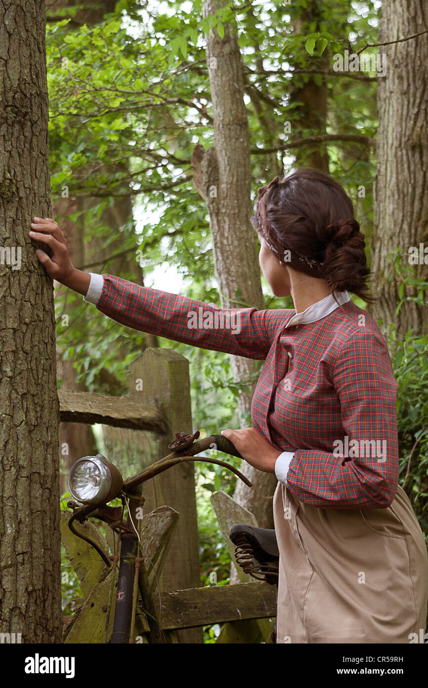 young woman in vintage dress standing with old bicyle in woods - Stock Image