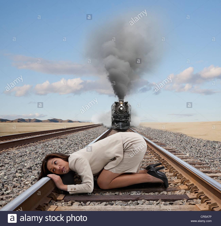 Mixed race businesswoman kneeling on railroad tracks Stock Photo