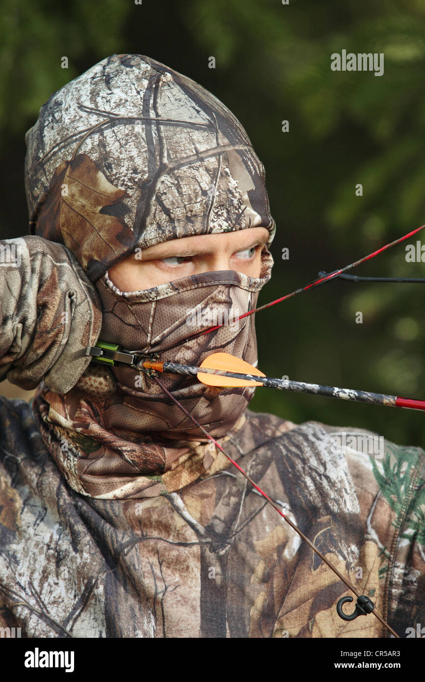 close-up bow hunter dressed in camouflage - Stock Image