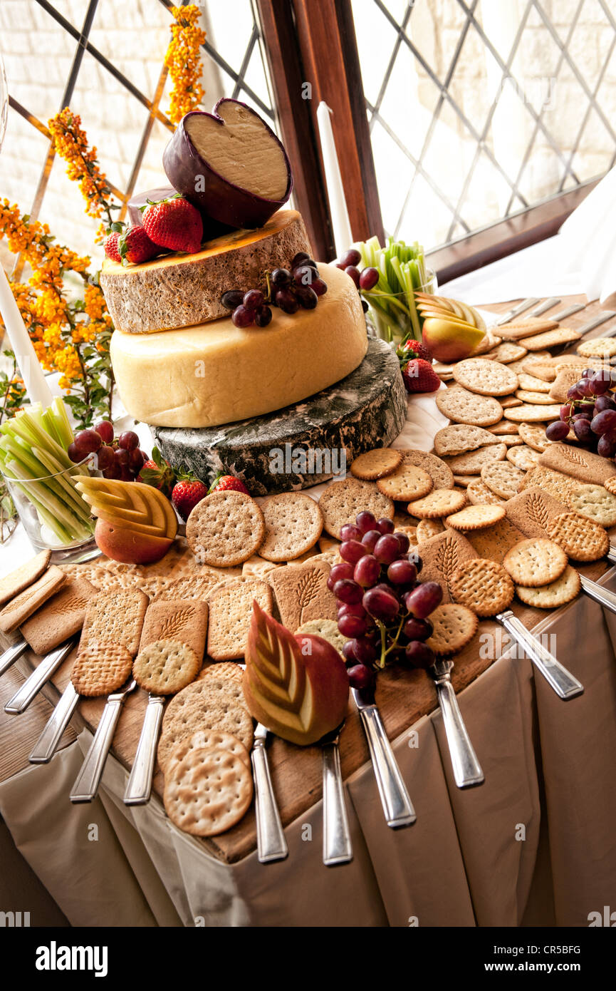 A Cheese Cake Display With Crackers And Fruit Display