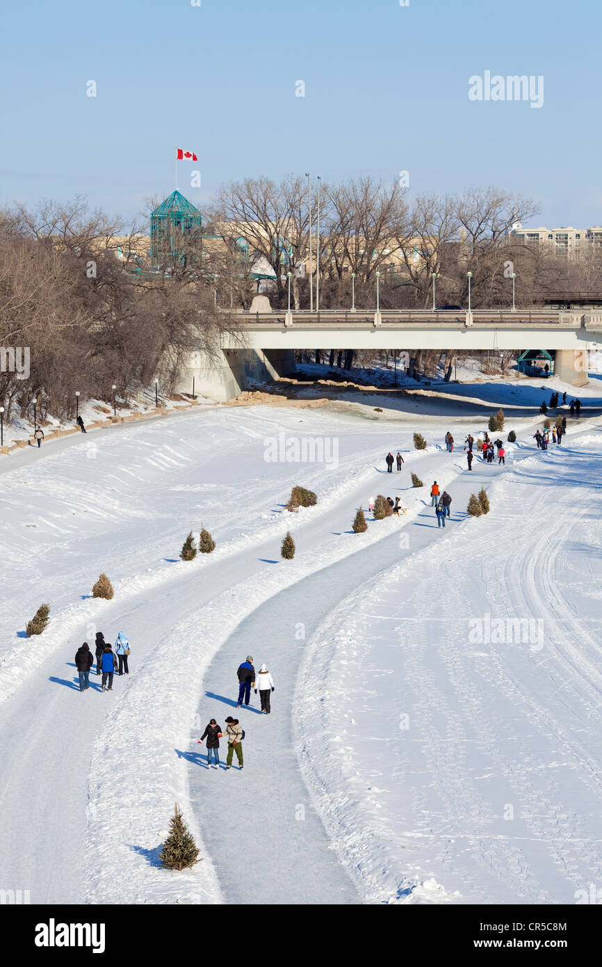 Canada, Manitoba Province, Winnipeg, The Forks, ice rink on the Red River of the North frozen in Winter, skaters - Stock Image