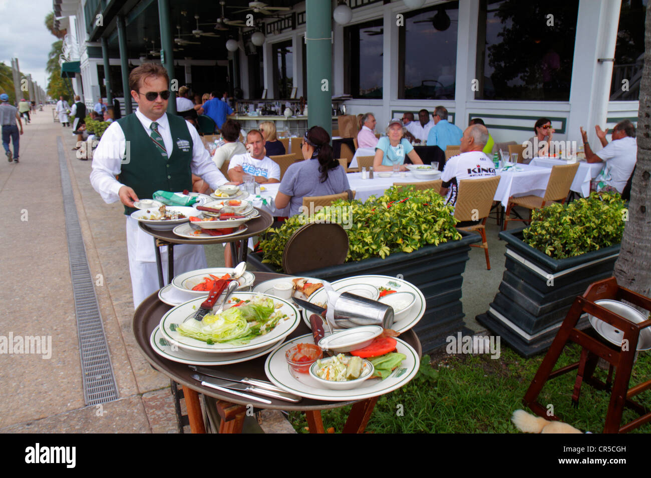 Miami Beach Florida South Pointe Smith and & Wollensky restaurant alfresco dining waiter man diners dirty plates - Stock Image