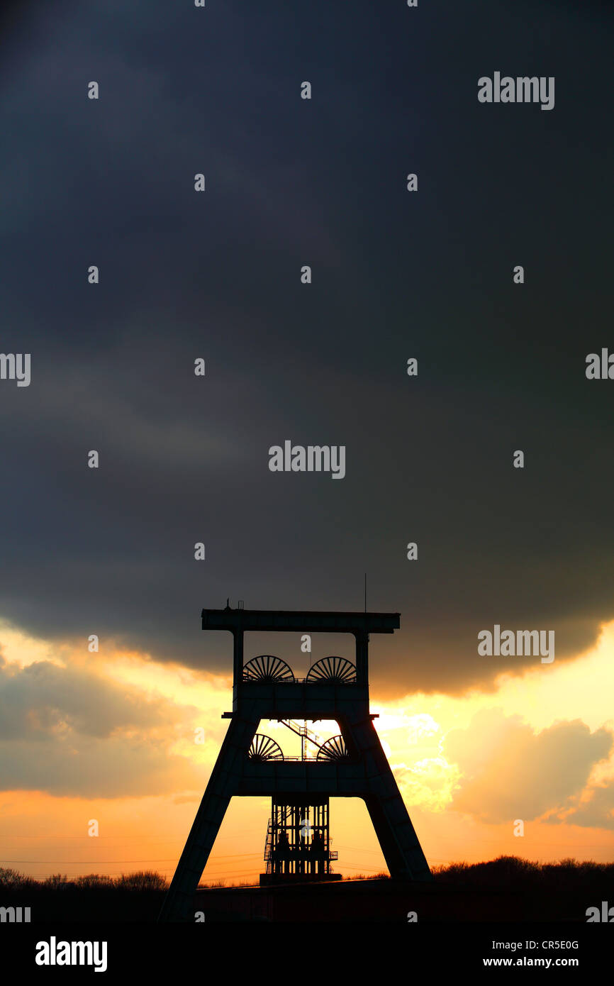 Winding tower of a former coal mine, sunset, dark sky, clouds. Symbol for the end of the coal mining in the Ruhr - Stock Image