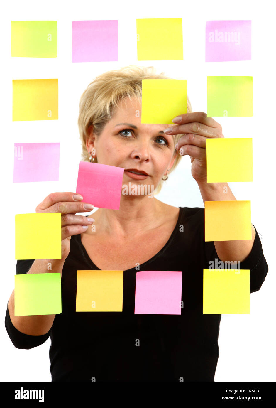 woman sticks self-adhesive Post It, paper notes, stuck to a pane of glass. Different colors. - Stock Image