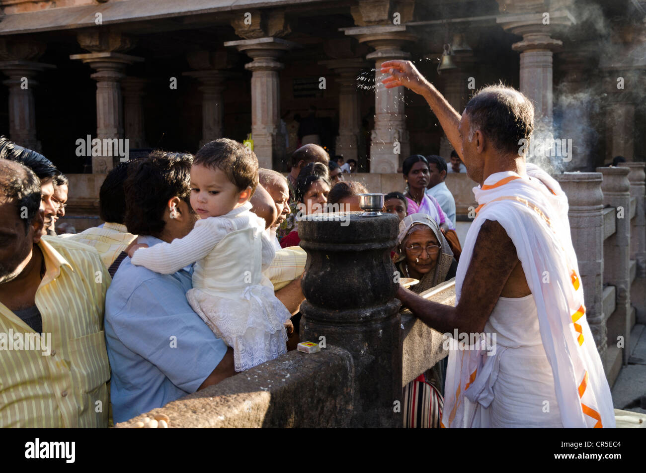 Pilgrims receive the blessings of Bahubali by a local priest on Indragiri hill in Sravanabelagola, Karnataka, India, - Stock Image