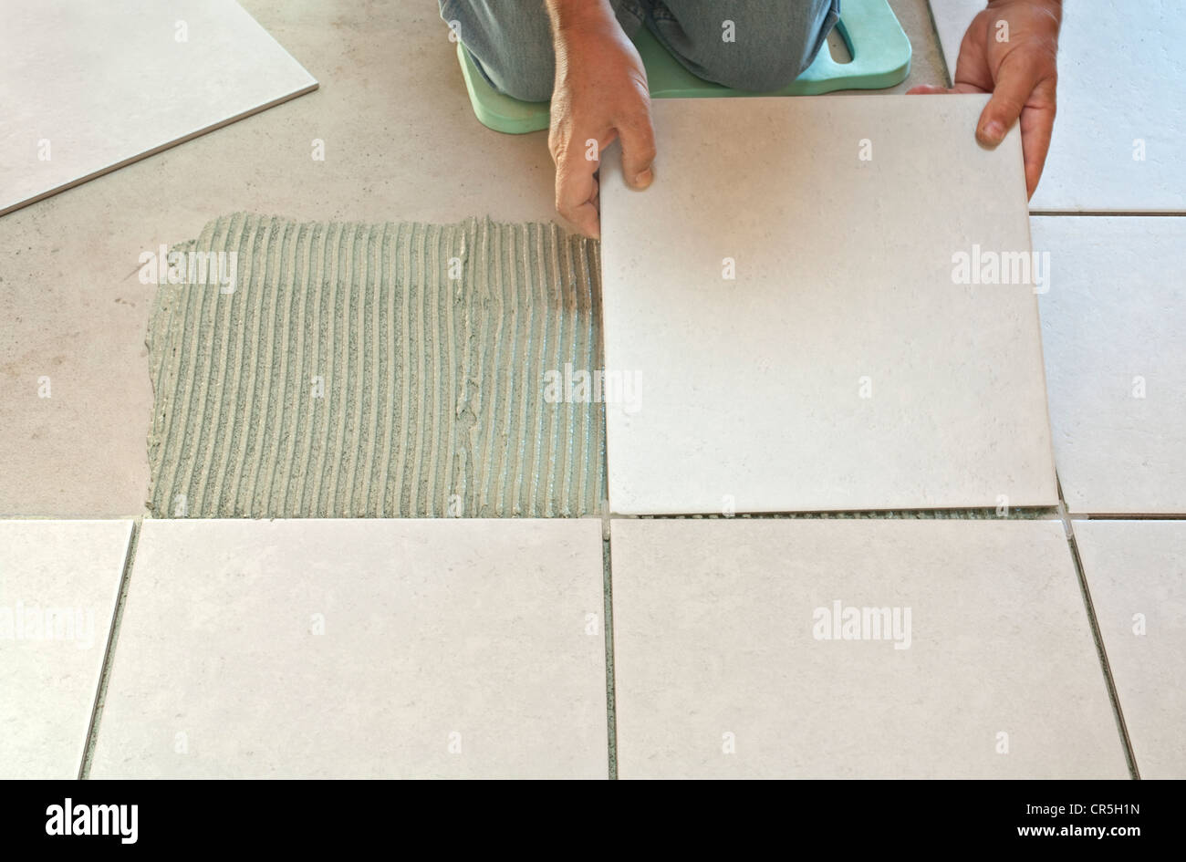 Man placing ceramic floor tile in position over adhesive. - Stock Image