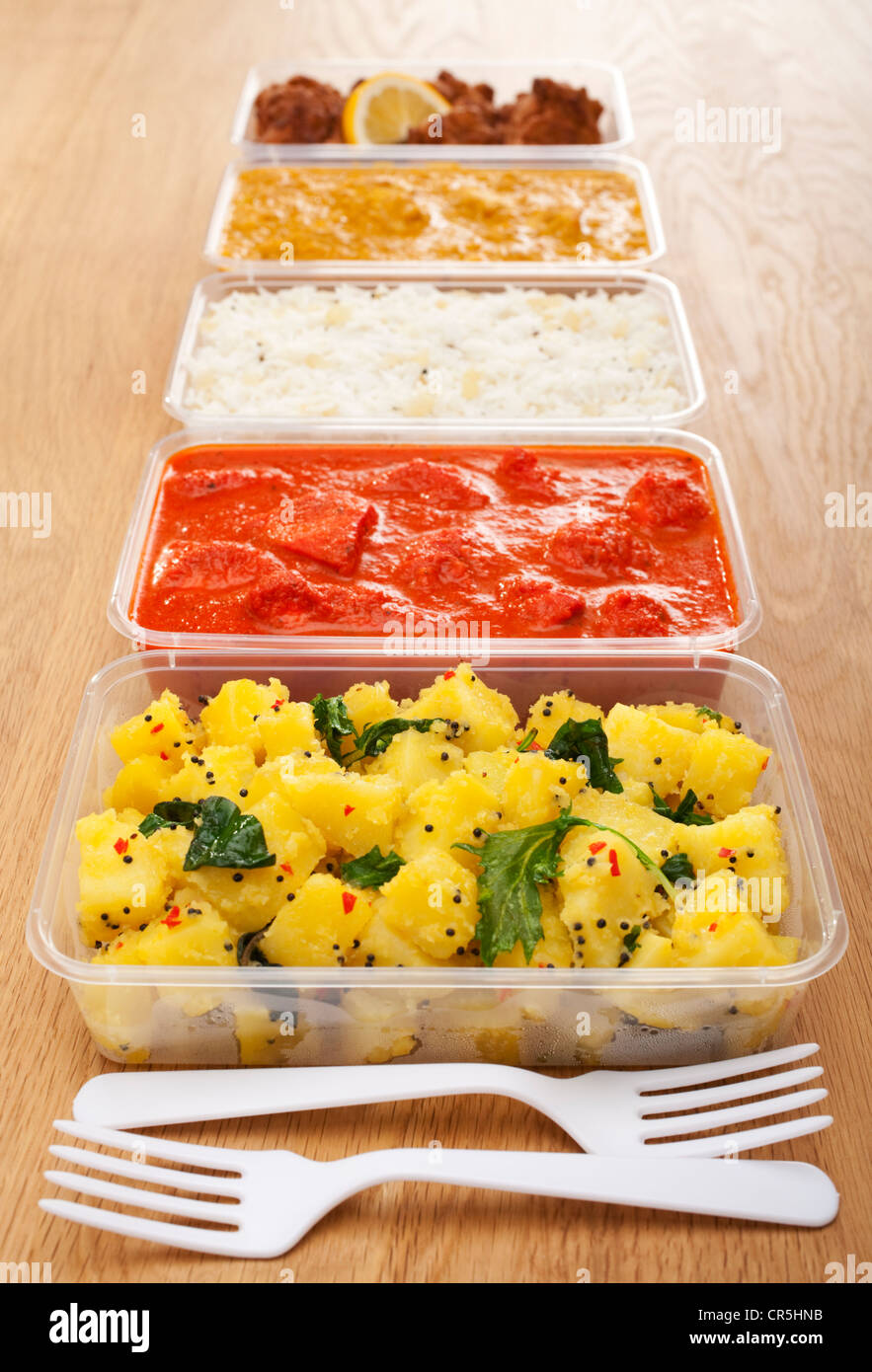 A selection of Indian takeaway food in plastic containers on a wooden table - Stock Image