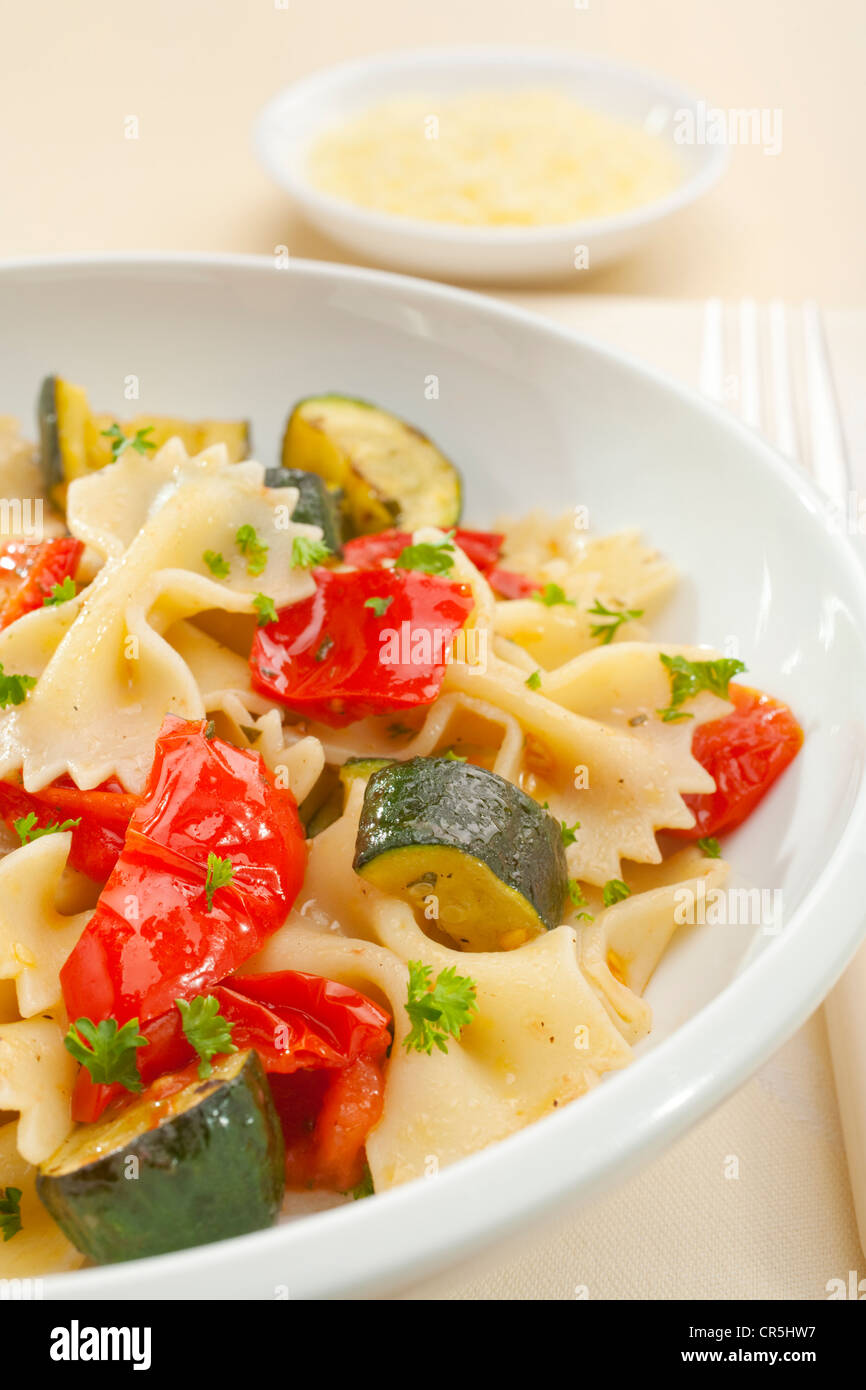 A bowl of pasta bows or farfalle with roast courgettes or zucchini, red pepper and tomato with olive oil and herbs. - Stock Image