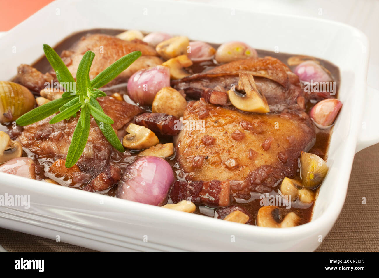 French classic, coq au vin or chicken in red wine with mushrooms, onion and bacon. Perfect for Sunday lunch with - Stock Image
